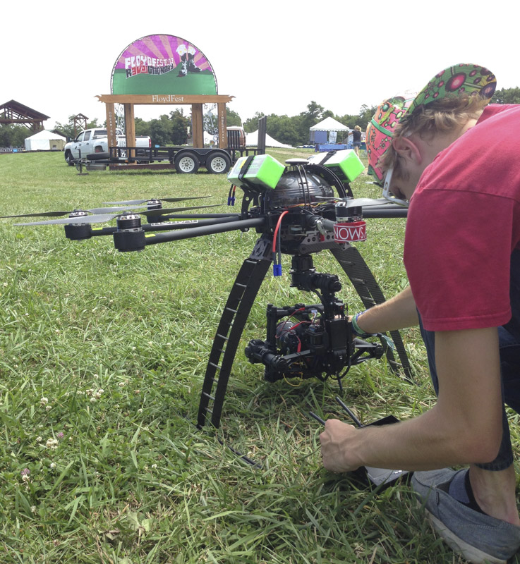 nowsay zach preparing camera on skyjib drone before takeoff