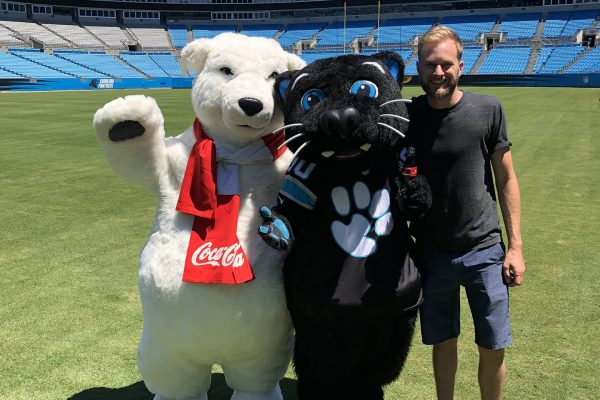 zach with sir purr and coca cola polar bear on carolina panthers field